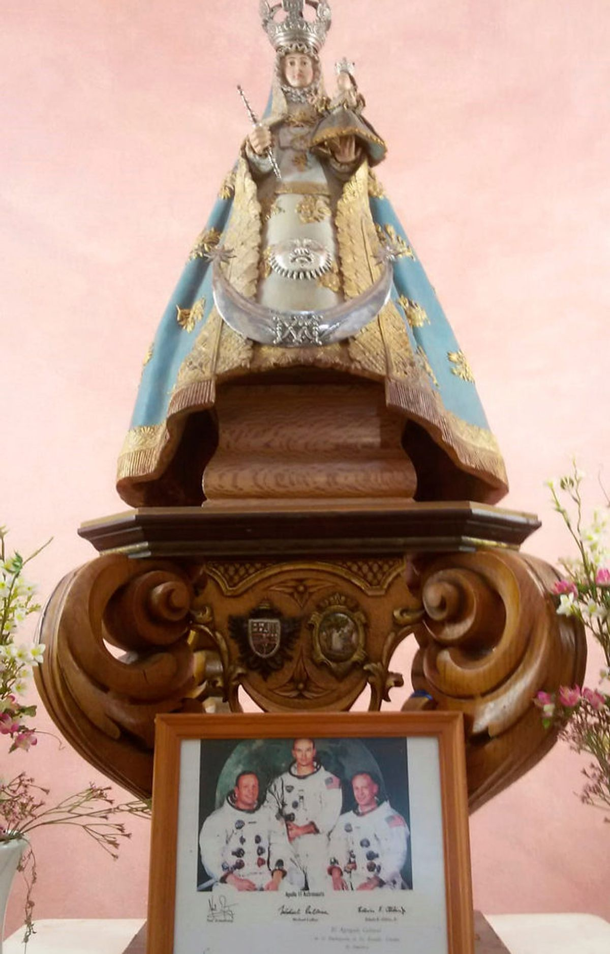 Imagen de la Virgen de Luna junto a la foto firmada de los tres astronautas que viajaron en el 'Apollo 11